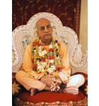 Srila Prabhupada on Cream Colored Vyasanasna with Many Flower Garlands